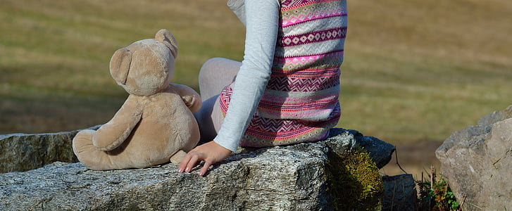 person sitting beside brown bear plush toy during daytime