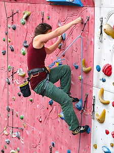 photo of woman in red tank top doing wall climbing