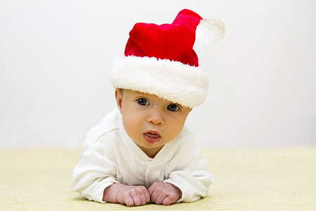 baby wearing red Santa hat crawling on floor