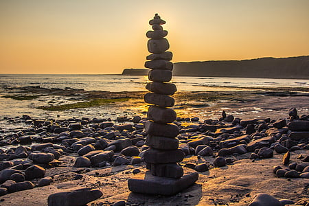gray boulder pillar near body of water