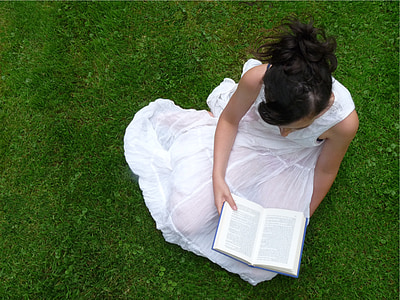 woman seating on grass reading book
