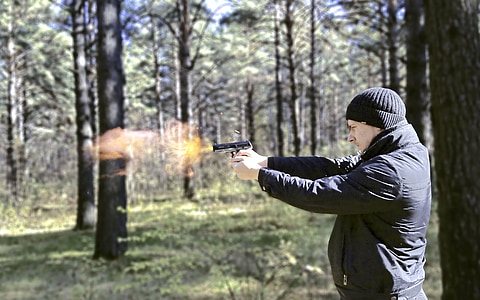man firing semi-automatic rifle in a forest during daytime