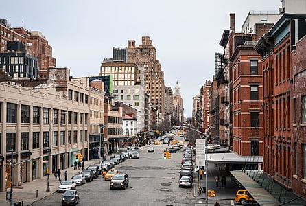 brown and beige concrete buildings between cars on street