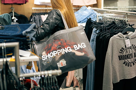 woman in black leather jacket carrying clear shopping shoulder bag