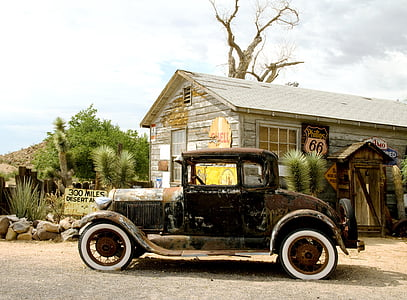 photography of black Ford Model A near gray house