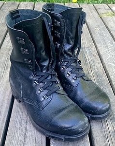 pair of black leather work boots on brown surface