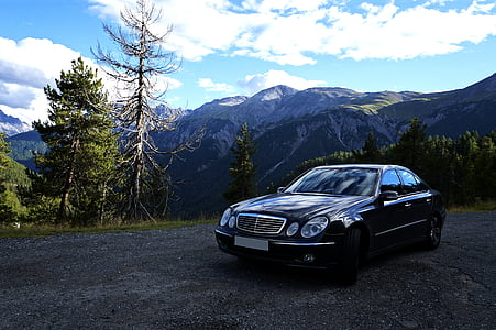 black Mercedes-Benz sedan near trees during daytime