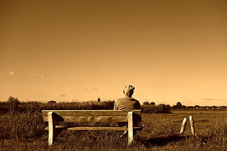 grayscale photography of man sitting on bench