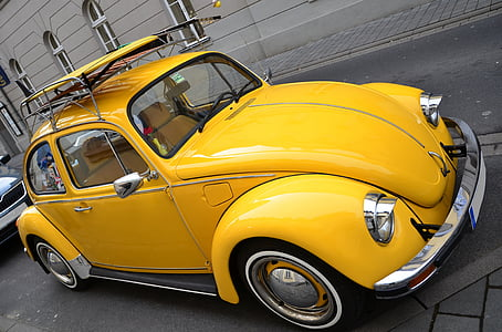 yellow Volkswagen Beetle couple on roadway near gray building