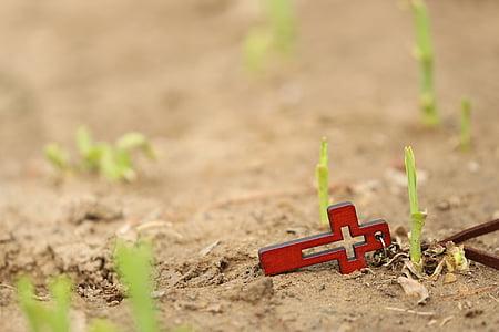 orange wooden cross pendant on brown sands