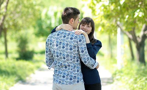 man hugging woman on road
