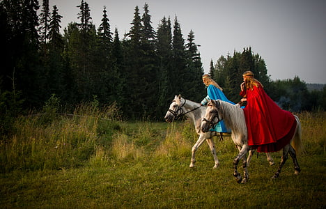 two women riding white horses