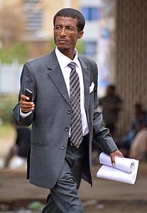 person wearing gray blazer holding white printer paper