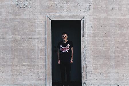 man in black shirt standing on doorway