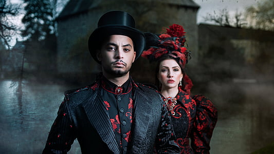 man wearing black suit and woman wearing black and red floral dress wallpaper