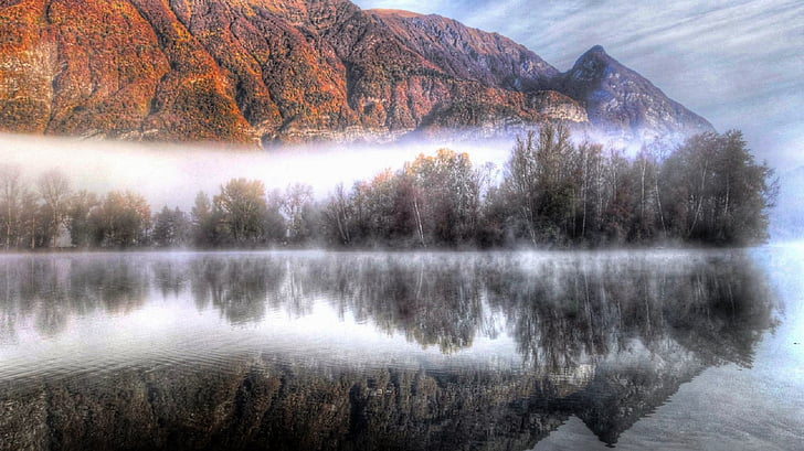 calm lake near orange mountain during daytime