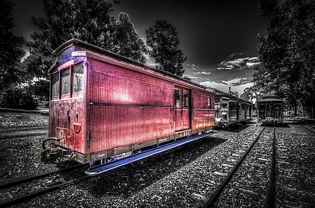 selective color photography of train under cloudy sky