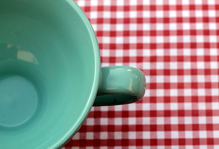 green cup on white and red gingham mat