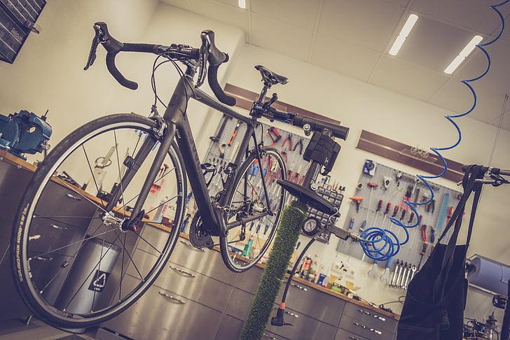 black road bike beside green stand