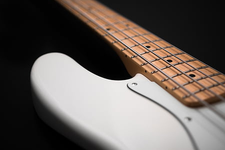 closeup photography of white and brown 4-string bass guitar