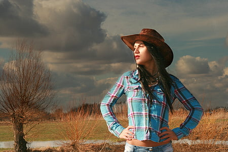 woman in blue and red sport shirt and brown cowboy hat near green sand
