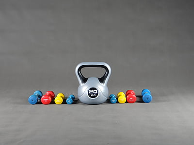 gray kettle bell and fixed weight dumbbells