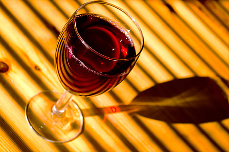 photography of footed glass with wine