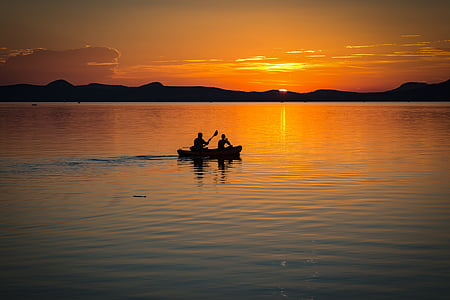 silhouette photography of two person on boat sailing during golden hour