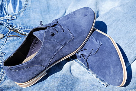 pair of blue suede chukka shoes on blue denim shorts -