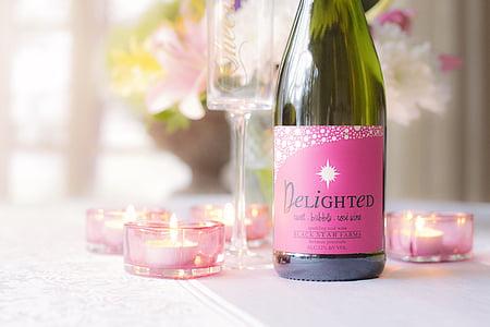 Delighted liquor bottle beside tealight candles
