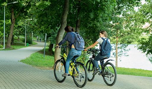 two women riding on mountain bikes on street during daytime