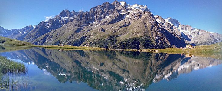 photo of mountain range with reflection on body of water