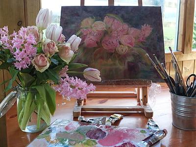 flowers on vase beside painting