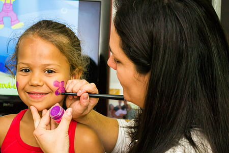 woman painting a purple flower on the face a girl