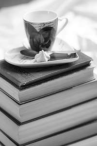 greyscale photo of teacup on top book stack