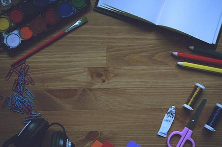 purple scissors on brown wooden surface