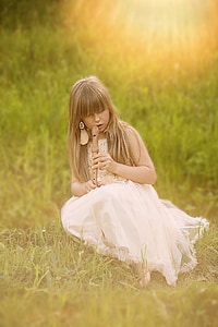girl sitting on grass while playing wooden flute