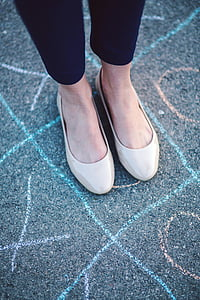 person in black pants and pair of beige patent leather shoes