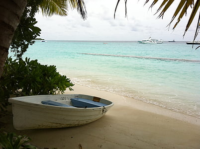 white rowboat on beach with calm sea at daytime