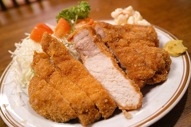 breaded chicken with white ceramic plate on brown table