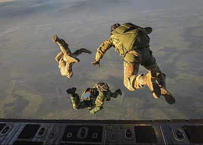 army jumping off plane with parachute backpack