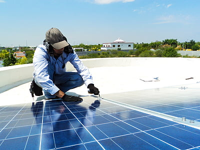 man repairing solar panel