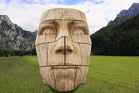 photo of brown wooden human's face on top of green grass during daytime
