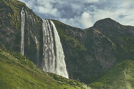 waterfalls on the mountain during daytime
