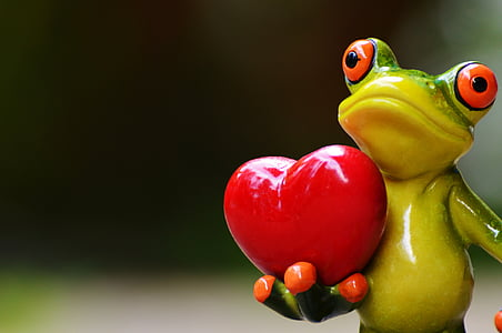 ceramic green frog carrying heart selective focus photography