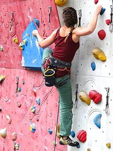 woman climbing on wall