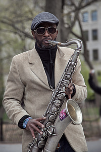man in brown suit playing gray saxophone