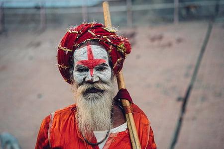 man wearing red top holding brown stick