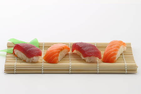 four salmon sushi on brown wooden mat