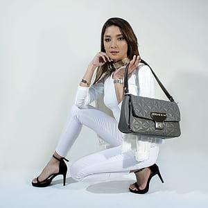woman holding gray hobo bag